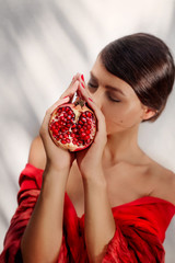 attractive young woman in red dress with pomegranate at white ba