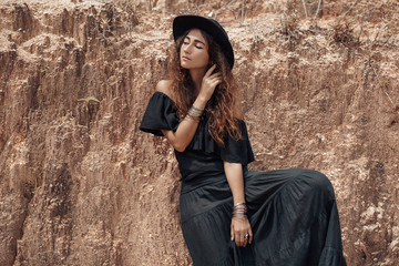 beautiful woman in black dress and hat posing at stone wall back
