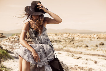 attractive boho girl siiting on stone outdoors