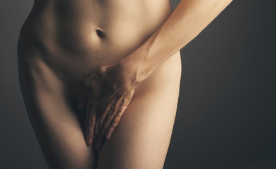 part of a nude woman body with close hands between the legs in