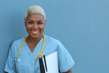 Young happy afro american nurse standing at hospital ward with clipboard and pen in hand. Smiling, looking at camera.