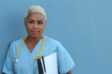 Young serious afro american nurse standing at hospital ward with clipboard and pen in hand. Neutral expression, looking at camera.