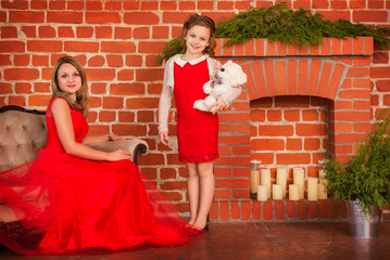 Mother and daughter in elegant dresses near fireplace christmas holiday