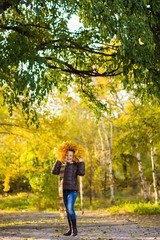 a teenager girl in jacket and jeans plays in the autumn park with golden leaves