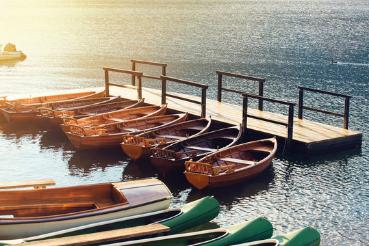 Small wooden boats and canoes tied to empty pier
