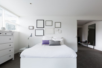 Bedroom with collection of blank frames on the wall