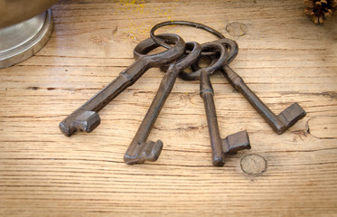 Rusty antique keys on wooden table as background