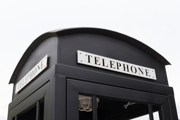 Vintage big black pay phone.