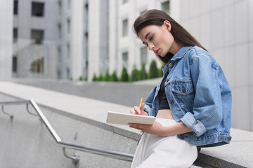 young fashion designer sketching outdoors