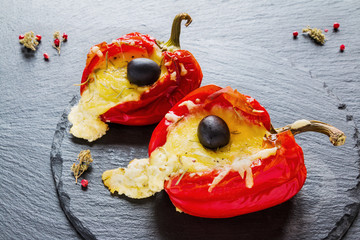 Stuffed red sweet peppers with feta cheese  and olives on black stone background.