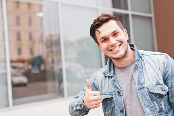 Young successful smiling man businessman in casual jeans jacket showing thumbs up gesture outdoors on street in summer in front of mirror glass office building or business center