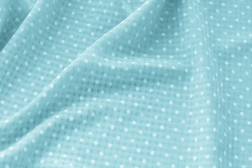 green polka dot fabric ,Creased green polka dot cloth material fragment as a background