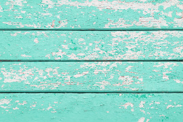 Old wooden planks with cracked turquoise paint
