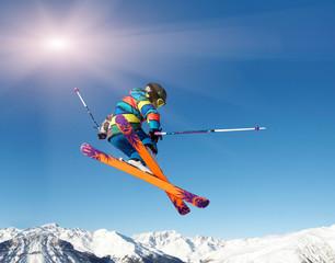 Skifahrer springt vor blauem Himmel und Sonne