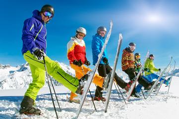 Gruppe Skifahrer in der Reihe mit einem Ski hoch