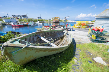 Dilapidated old fishing boat rests on the rocky shore of a fishing village in Peggy's Cove, in Halifax, Nova Scotia, Canada