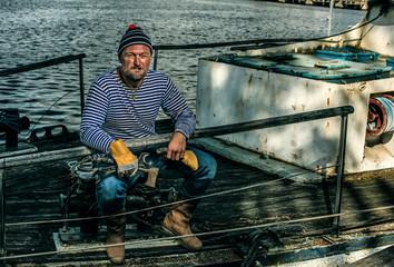 Old salt man smoking on his rusted ship