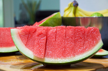 Watermelon without seeds cut in slices on wooden table