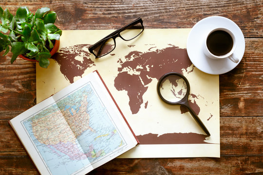 world map with coffee on wooden table top view