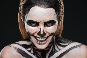 Smiling young woman with skeleton halloween makeup laughing
