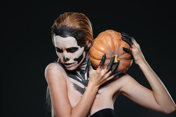 Woman with scared halloween makeup holding pumpkin