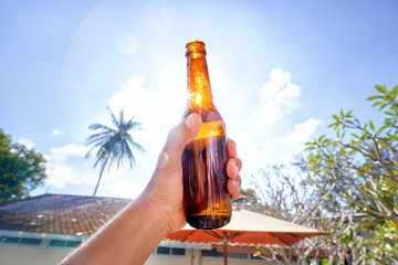 Vacation concept. Male hand holding bottle of beer against sunny sky.