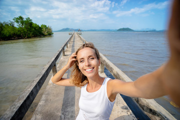 Vacation and technology. Young smiling woman taking selfie while walking on sea bay pier.