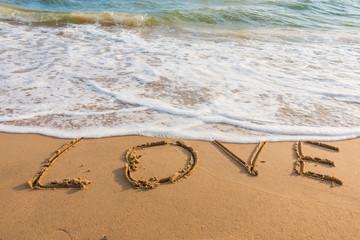 alphabet letters love handwritten in sand on beach