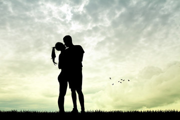 man and girl kissing at sunset