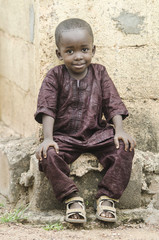 Handsome Little African Boy Sitting Outdoors whit a gentle smile on his face