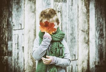 Kind vor Holzwand