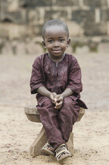 Sitting boy outdoors - African proud child