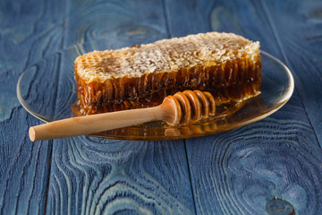 Honeycomb and honey dipper on wooden background