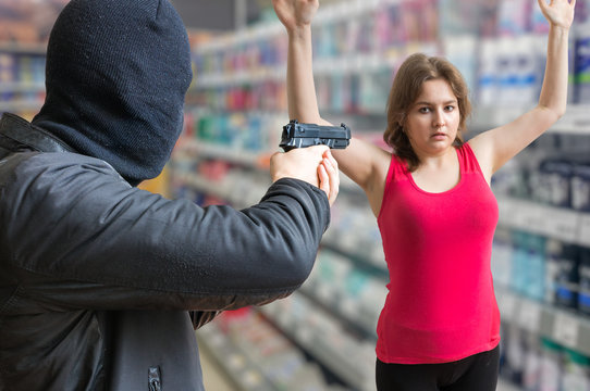 Robbery concept. Man in balaclava is aiming on woman in store.