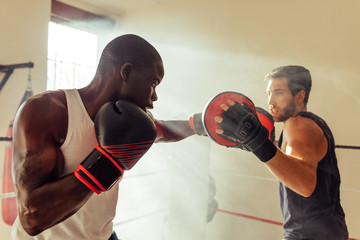 Man hitting focus mitts of boxing trainer