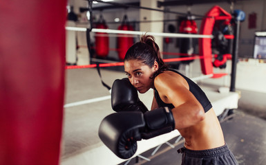 Female boxer training with punching bag