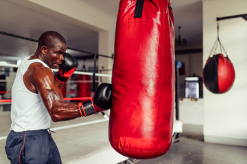 Muscular African boxer practicing his punches