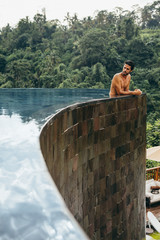 Man leaning at edge of infinity pool in tropical resort