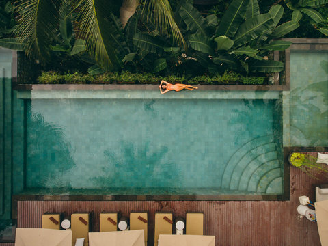 Woman lying on poolside in tropical resort