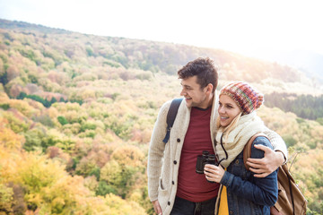 Young couple on a walk in sunny autumn forest