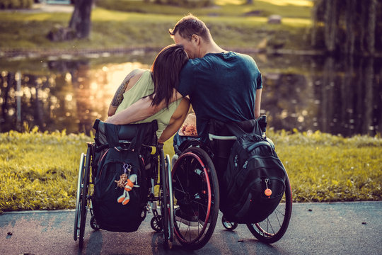Handicapped young couple in wheelchairs in autumn park