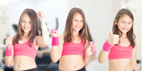 little girl with dumbbells  in fitness hall