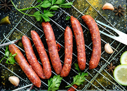 Raw sausages merguez, on a black background, with spices on the gridiron
