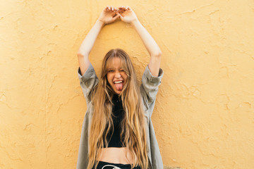 Pretty young girl with long blonde hair on yellow textured wall