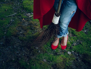 Witch legs in red shoes standing in the woods with a broom in his hand.