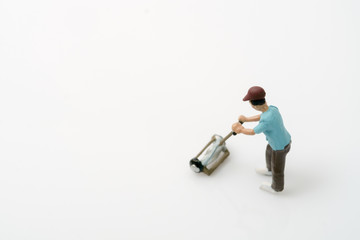 Toy people / View of miniature toy worker with lawn mower on white background.