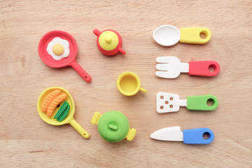 Toy kitchenware / View of miniature toy kitchenware on wood background. Top view. Flat lay.