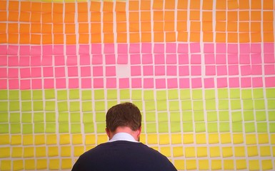 Rear View Of Businessman Against Colorful Adhesive Notes On Wall In Office