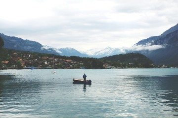 Man In Boat Fishing In Lake Against Sky