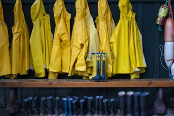 Yellow Raincoats And Rubber Boots Arranged Outdoors